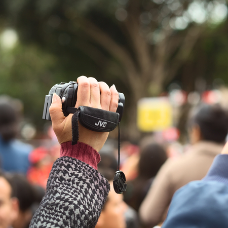 fiestas: LIMA, PERU - JULY 21, 2013  Unidentified person holding a video camera to film the Wong Parade in Miraflores on July 21, 2013 in Lima, Peru  The Parade  Gran Corso de Wong  is a traditional parade to celebrate the Peruvian national holiday which is on Jul