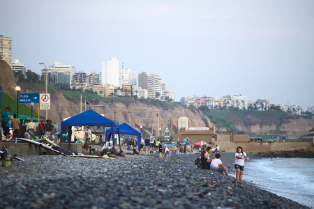 miraflores: LIMA, PERU - APRIL 2, 2012  Unidentified people on the rocky Pacific coast of Miraflores on April 2, 2012 in Lima, Peru  On the top of the steep coast the modern residential buildings of Miraflores can be seen