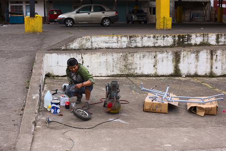 1 person: BANOS, ECUADOR - AUGUST 1, 2014: Unidentified person spraying a metal frame with grey color opposite a small bike repair shop on Juan Leon Mera street on August 1, 2014 in Banos, Ecuador.
