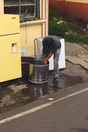 tungurahua: TUNGURAHUA, ECUADOR - MAY 12, 2014: Unidentified person cleaning a washing drum with water and brush on the roadside along the road between Ambato and Banos on May 12, 2014 in Tungurahua Province, Ecuador