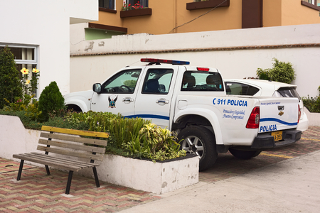 police unit: QUITO, ECUADOR - AUGUST 6, 2014: Police car parking in front of the building of the UPC (Unidad de Policia Comunitaria, Communitary Police Unit) on Gil. Ramirez Davalos Street on August 6, 2014 in Quito, Ecuador