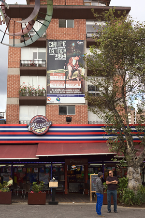 QUITO, ECUADOR - AUGUST 6, 2014: Players Sports Bar and Grill on Plaza Foch in La Mariscal on August 6, 2014 in Quito, Ecuador. The big sign says that there is a fine of 954 USD for drinking in public areas in the tourist districts.