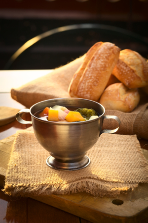 Fresh vegetarian soup made of broccoli, squash, onion, carrot, potato and tomato served in a metal cup on jute cloth and wooden board with ciabatta buns in the back, photographed with natural light (Selective Focus, Focus on the squash pieces in the middl photo
