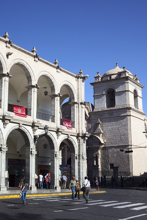 AREQUIPA, PERU - AUGUST 22, 2014: Paseo Portal de Flores and tower of the Iglesia de la Compania at the Plaza de Armas (main square) on August 22, 2014 in Arequipa, Peru. The historic city center of Arequipa is an UNESCO World Cultural Heritage Site.