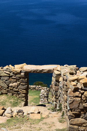 View through a door frame of the Chinkana archeological site of Tiwanaku (Tiahuanaco) origin on the Northwestern part of the Isla del Sol (Island of the Sun) in Lake Titicaca in Bolivia. Isla del Sol is a popular tourist destination and is reachable by bo photo