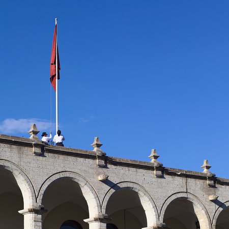 AREQUIPA, PERU - OCTOBER 8, 2014: Unidentified women pulling up the flag of Arequipa onto a flagpole on top of the city hall along Portal de la Municipalidad at the Plaza de Armas (main square) in the morning on October 8, 2014 in Arequipa, Peru