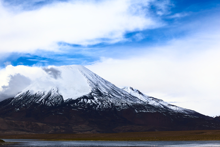 Parinacota stratovolcano (6348 meters) and Chungara Lake on the border of Chile and Bolivia on the way from La Paz to Arica. Parinacota is part of the Payachata volcanic group in Northern Chile. photo