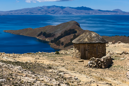 Small round stone hut with thatched roof on Isla del Sol (Island of the Sun) in Lake Titicaca, Bolivia. The island is a popular tourist destination. photo