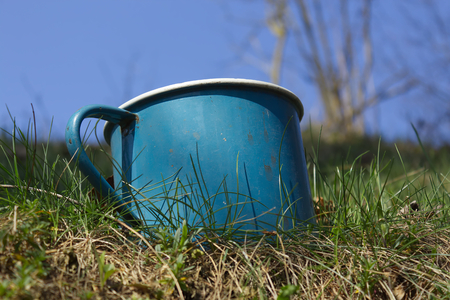 Old enamel metal battered mug grass garden with sky background Foto de archivo