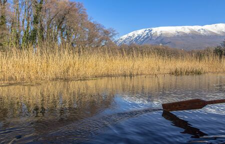 The incredible colors of the springs that flow into Ohrid Lake. Against the background of reeds, trees and snowy hills on the mountain. With a boat paddle.