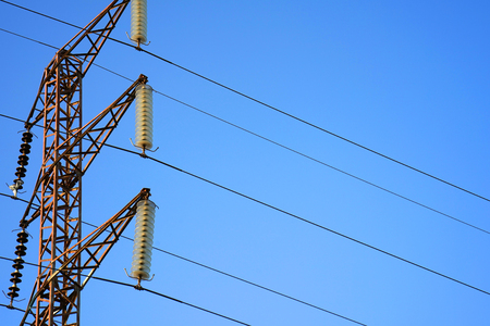 High voltage electric poles on blue sky background