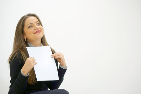 Smiling woman reading letter while sitting on sofa in front of laptop. Happy lady enjoying good news in written notice. Euphoric girl happy after reading good news in written letter, loan approvale.