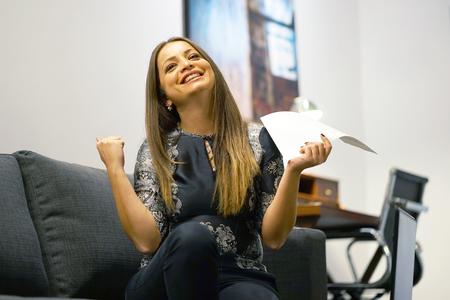 Happy brunette enjoying good news in written notice. Euphoric girl happy after reading good news in written letter, loan approvale.