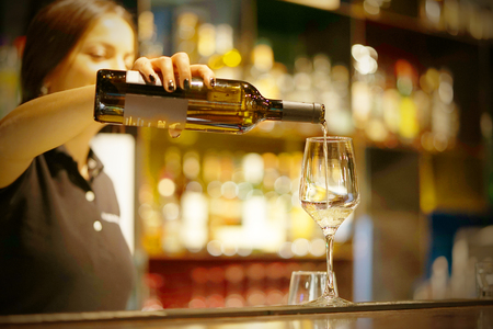 A barman girl standing smiling, pours white wine into a glass from a bottle. Shelves with bottles of alcohol in the background. Focus on the glass Standard-Bild