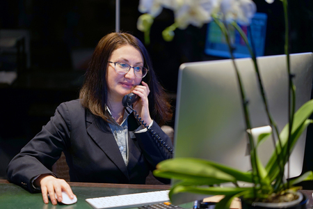 Hotel administrator. A woman-reception worker accepts an order for booking a room by phone. Profile shot of attractive executives at the reception of a hotel. The concept of service. Stock Photo