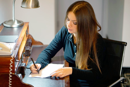 A young woman concentrates while writing a letter on her desk at home. Vertical shot. A girl is writing a letter to get out of work. The concept of family and personal life.