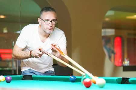 A man plays a billiard at the club. Young man playing spending time on recreation. Play and fun concept.