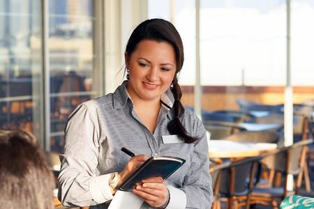 The waitress takes the customers order in the hotel restaurant. Lunch time. The girl smiles cute. A young woman waiter takes an order. The concept of service. Stock Photo