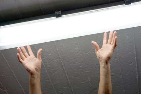 Electric hands changing ceiling fluorescent lamp. The concept of repair and service. Stock Photo