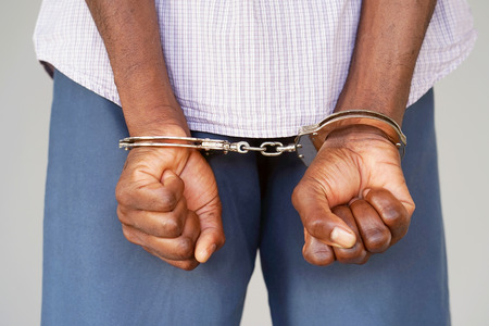 Close-up. Arrested man handcuffed hands at the back. Prisoner or arrested terrorist, close-up of hands in handcuffs, selective focus.