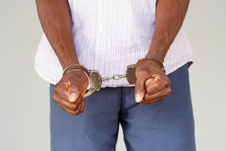 Close-up. Arrested man with handcuffs in front. Prisoner or arrested terrorist, close-up of hands in handcuffs, selective approach. Stock Photo - 97279675