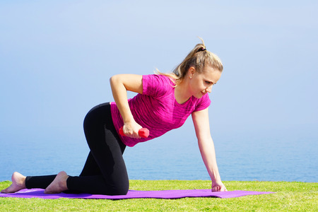 Young woman on grass with dumbbells in hands on the background of the sea. Fitness girl doing exercises with weights on the beach under the morning sun. The concept of health and weight loss. Stock Photo