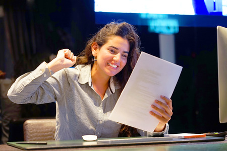Close-up of an office worker. Happy lady, enjoying the good news in writing. An euphoric girl is happy after reading good news in a written letter, approving a loan, raising her job.