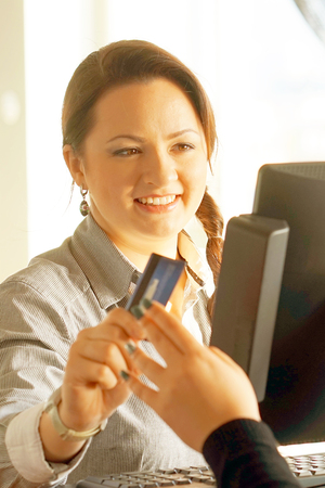 A restaurant worker registrating new order by cash-register. The waiter gives the card to the client. Toning