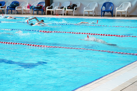 A group of people swimming in the pool. Male swimmers competing in a race. Anonymous athletes in a pool. Group of boys swimmers floating in the pool Stock Photo