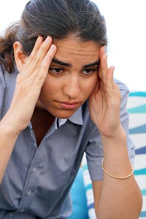 Mujer joven que sufre de dolor de cabeza dolor de migraña. Problema de salud, estrés y depresión. Mujer tiene la cabeza con la mano. Concepto de salud. Foto de archivo - 100717157