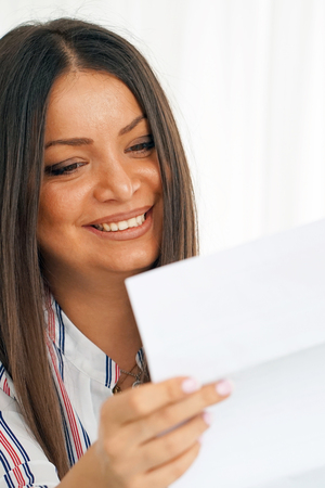 Woman enjoying good news in writing. The girl reads a letter with good news sitting on the couch. An euphoric girl is happy after reading good news in a written letter, approving a loan.