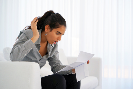 Woman reads negative news in a letter at home on the couch. The shaken business manager of the beauty girl received a notice of dismissal from the company, surprised. An agitated girl without joy.