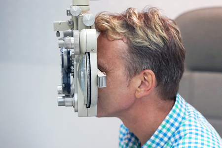 health care, medicine, people, eyesight and technology concept - man checks his vision on the machine checking patient vision at eye clinic or optics store. face close-up Stock Photo