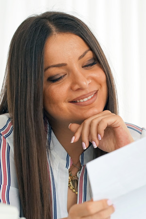 Woman enjoying good news in writing. The girl reads a letter with good news. An euphoric girl is happy after reading good news in a written letter, approving a loan.