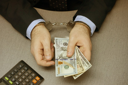Close-up. Businessman in office in handcuffs holding a bribe. Arrested man in handcuffs. Toning