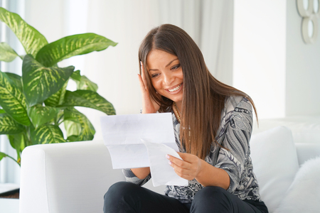 Young woman enjoying good news in writing. The girl reads a letter with good news sitting on the couch. An euphoric girl is happy after reading good news in a written letter, approving a loan.