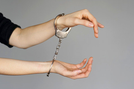 Arrested woman handcuffed hands. Prisoner or arrested terrorist, close-up of hands in handcuffs isolated on gray background. Criminal female hands locked in handcuffs. Close-up view