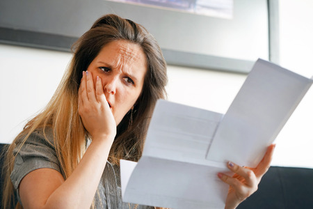 Close-up of an office worker. Woman reading negative news in letter. Shocked beauty girl business manager received. An agitated girl without joy.