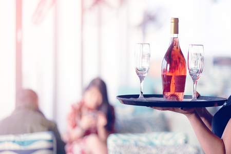 A young waitress carries a bottle of red wine with wine glasses on a tray to the customer of the hotel restaurant. The concept of service. Toning