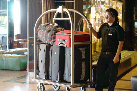 Closeup many suitcases on hotel luggage cart moving by bell boy. Baggage porter or bell boy bringing the suitcase of guests with a box van to the hotel room. Trolley Luggage at the hotel.
