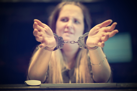 Arrested woman handcuffed hands. Close-up of office worker, Prisoner or arrested terrorist, hacker, bribetaker, close-up of hands in handcuff. Selective focus. Toning