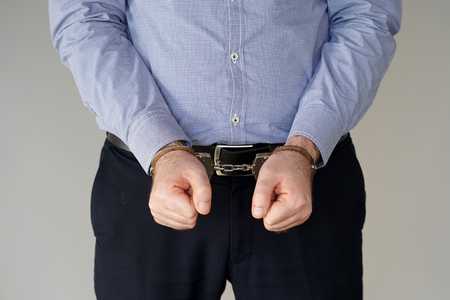 Close-up. Arrested man handcuffed hands. Businessman in office in handcuffs holding a bribe. Arrested man in handcuffs. Stock Photo - 104082816