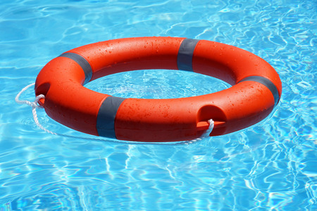 Red lifebuoy pool ring float on blue water. Life ring floating on top of sunny blue water. Life ring in swimming pool Stockfoto