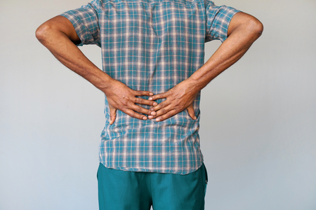 Close-up view of a young man with pain in kidneys on gray background. Young man with back ache clasping her hand to her lower back. Man suffering from ribbing pain, waist pain.
