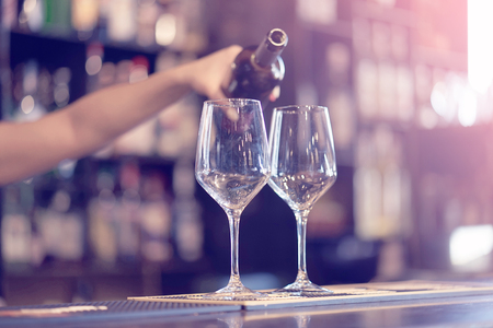Hand a barman girl pours white wine into a glass from a bottle. Shelves with bottles of alcohol in the background. Focus on the glass. Toning