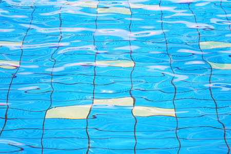 Pure blue water in the pool. Water background. Swimming pool bottom caustics ripple and flow with waves background. Water in swimming pool rippled water detail background. Stock Photo