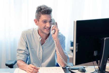 Hombre de negocios hablando por teléfono en el trabajo. Primer plano de un oficinista masculino contestando el teléfono y mirando un monitor de computadora en un centro de servicio al cliente. Recepcionista de hotel mediante computadora y teléfono