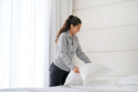 Maid making bed in hotel room. Stock Photo