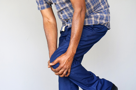 Pain In Knee. Close-up African Male Leg With Painful Kneeson on gray background. Man Feeling Joint Pain, Having Health Issues And Touching Leg With Hands. Body And Health Care Concept.