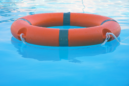 Red lifebuoy pool ring float on blue water. Life ring floating on top of sunny blue water. Life ring in swimming pool Stock Photo